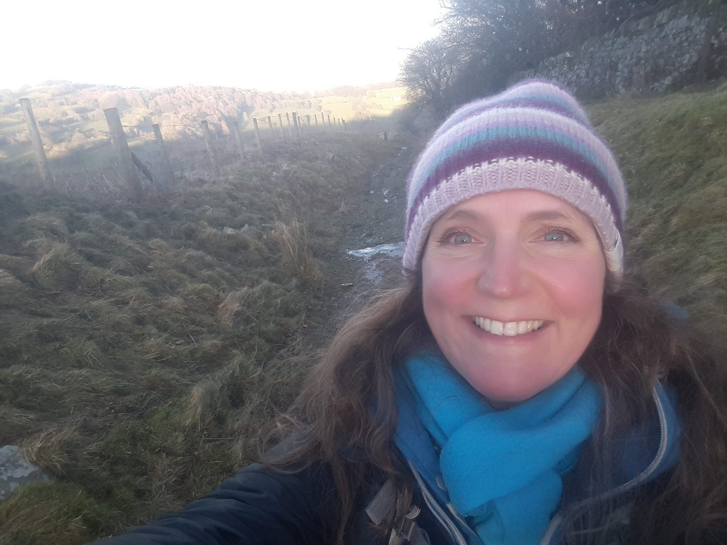 Zoe Langley-Wathen standing at the top of a path called the gully.  It is muddy and fenced on one side with a steep bank and dry stone walling on the other.  Zoe wears a stripey woollen hat, a blue scarf, blue and black jacket and a big smile.