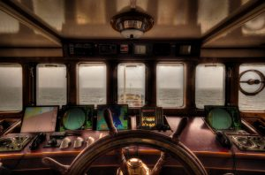 poop deck; ship cabin; ship's wheel; navigation charts