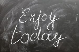 A blackboard with the words 'Enjoy today' written on in white chalk