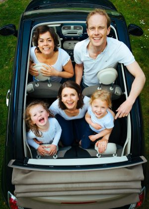 A family looking up out of an open top car, having fun