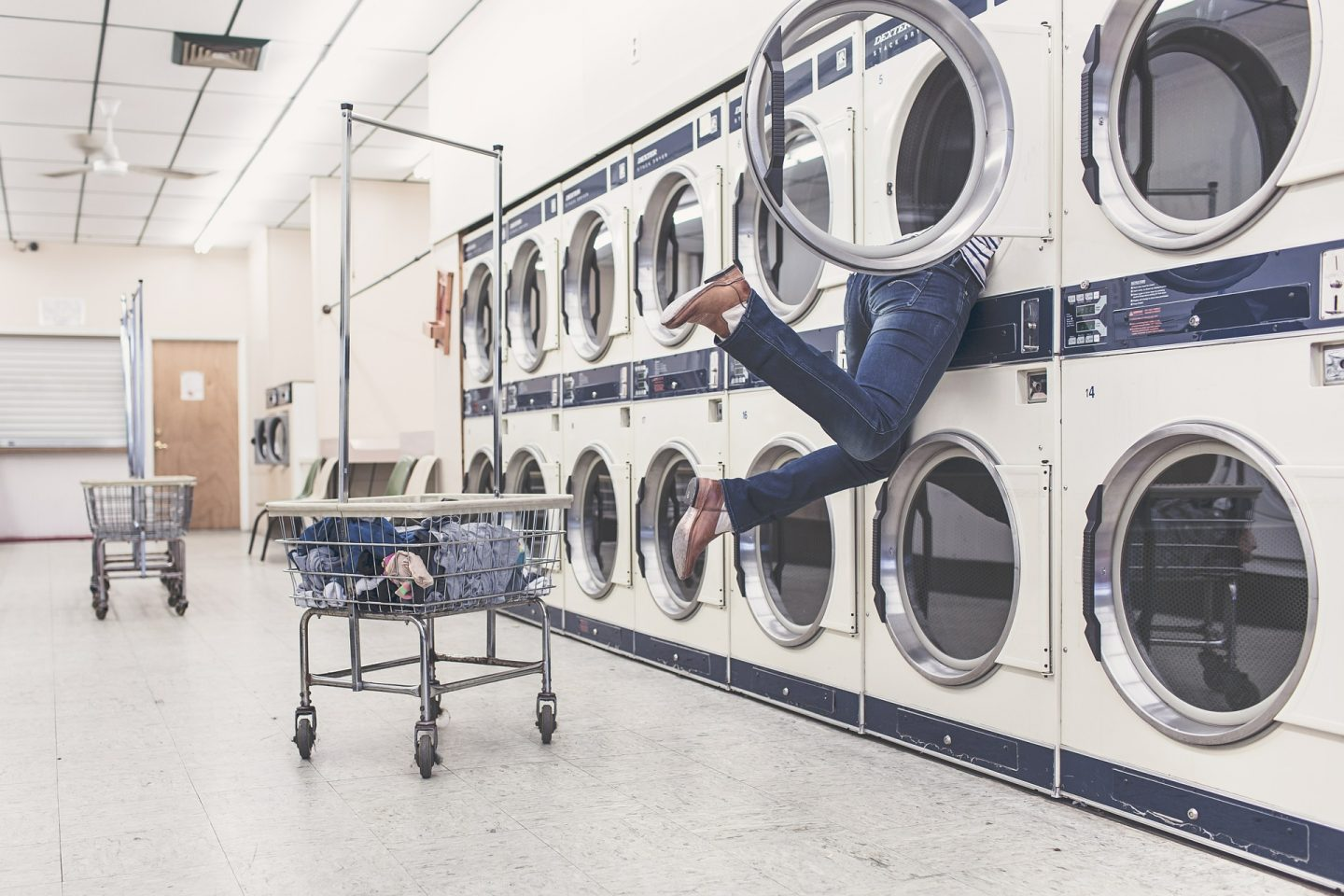 launderette with a woman head first inside a tumble drier, feet dangling