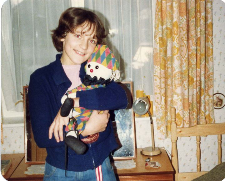 A twelve-year-old girl, with short hair and braces, standing in a bedroom and cuddling a toy clown.