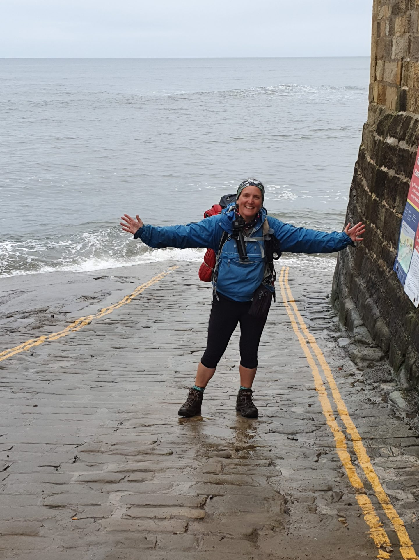 woman standing on the slipway into the water at Robin Hood's Bay with arms outstretched