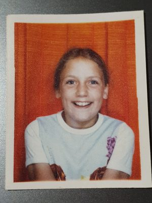 A young girl smiling to the camera inside a photo booth with an orange curtain for the background.