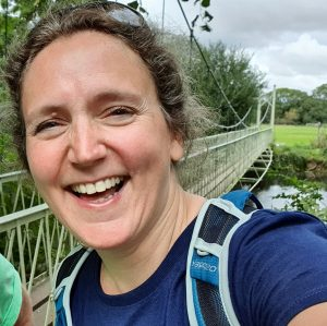 A woman laughing, at the side of a river with a long narrow suspension bridge in the background