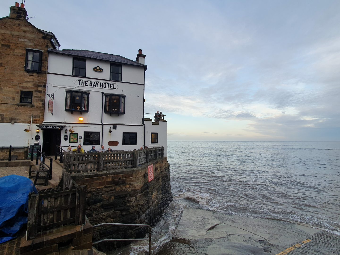The Bay Hotel perched on the edge of a harbour wall with sea to the right, dominating the photograph