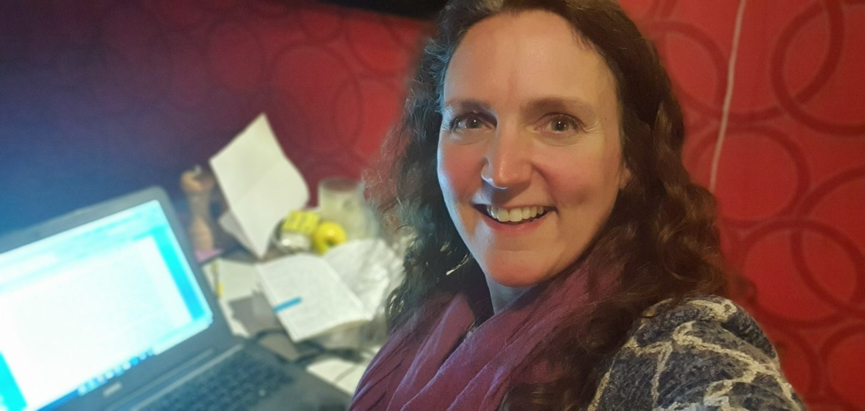 Woman sat at a computer screen but looking at the camera, smiling