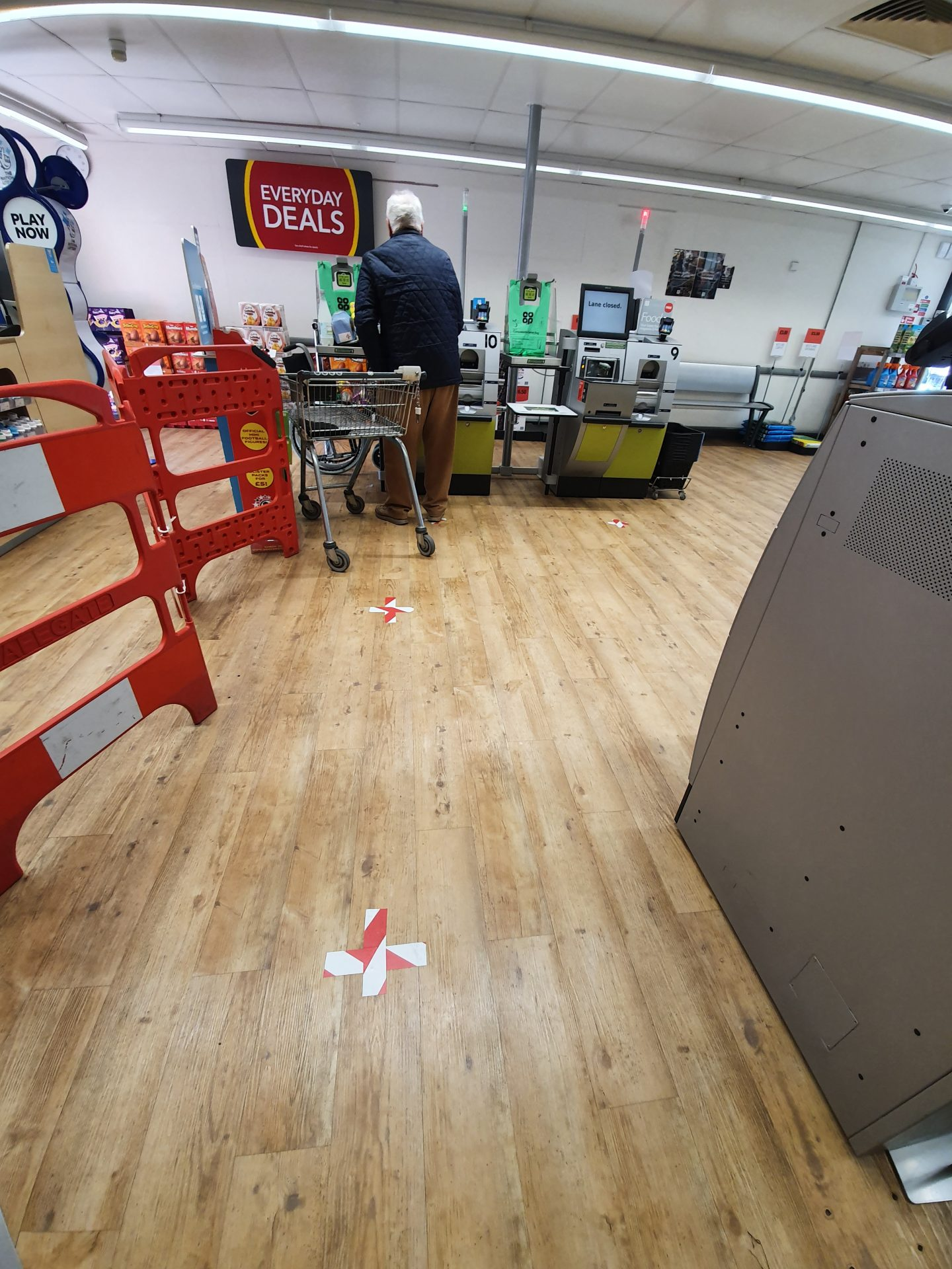 A mostly empty supermarket showing the self-adhesive tape on the floor, marking where people should stand
