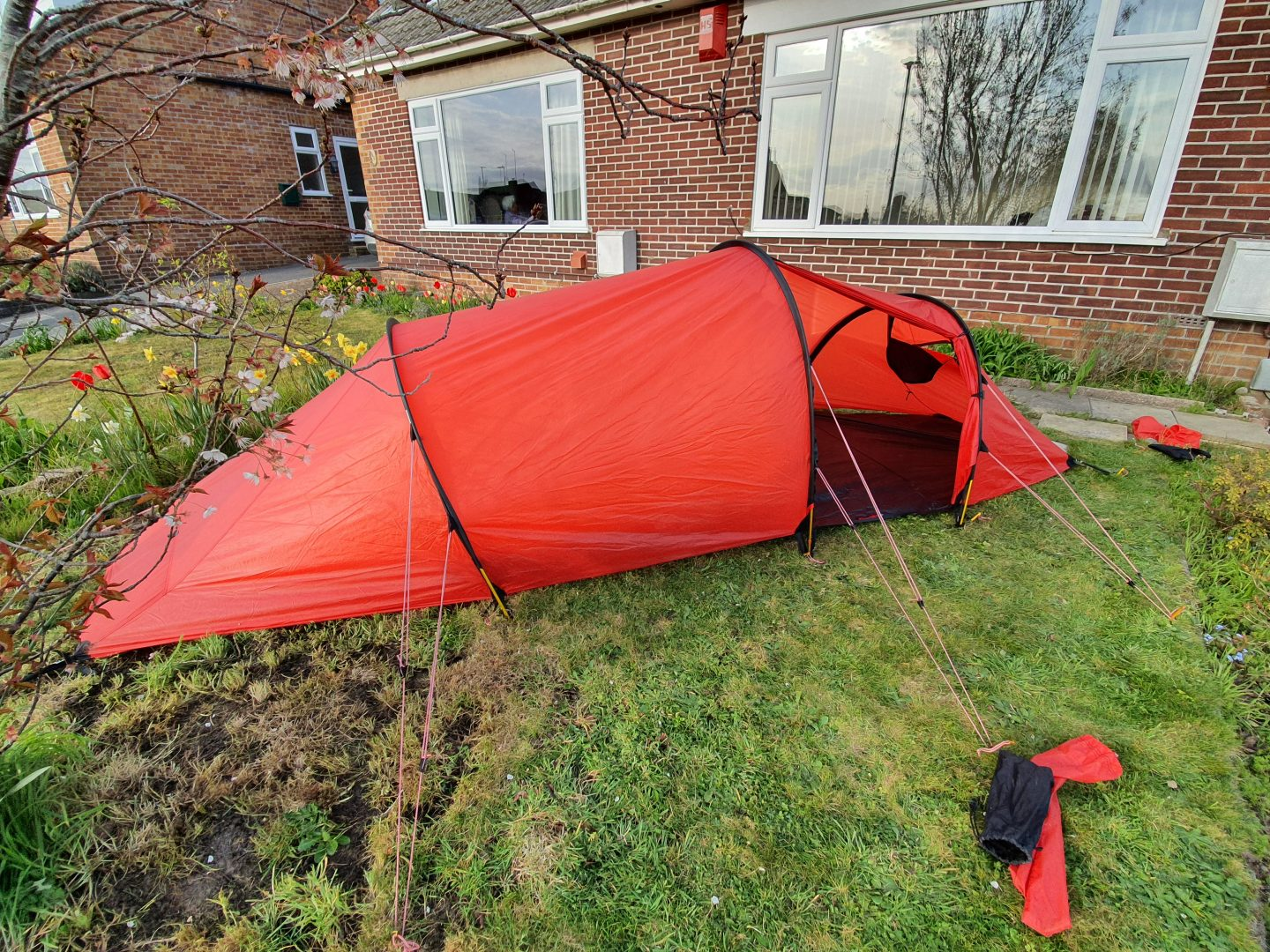 A red expedition tent pitched in front of a house