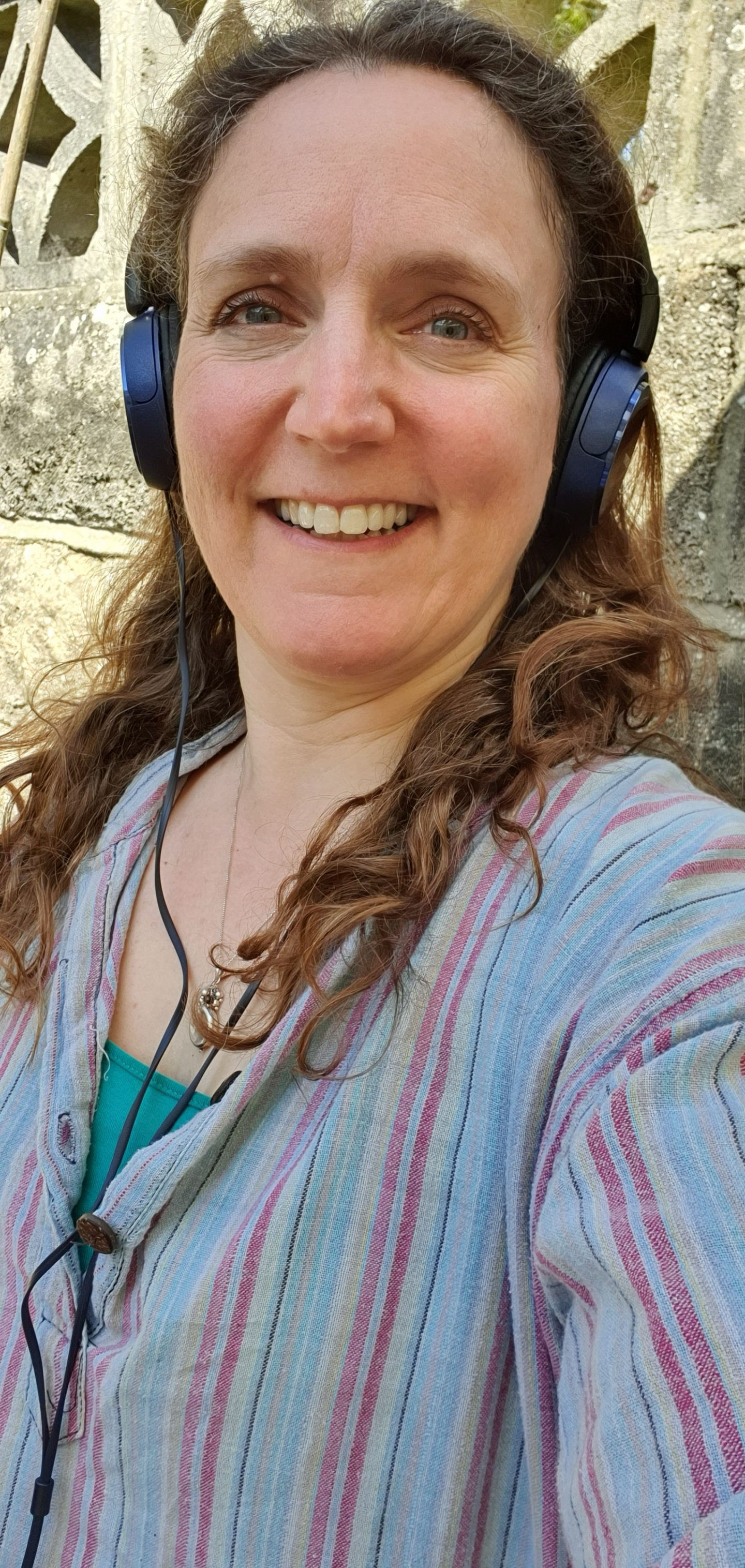 Woman standing in front of a wall smiling, wearing headphones