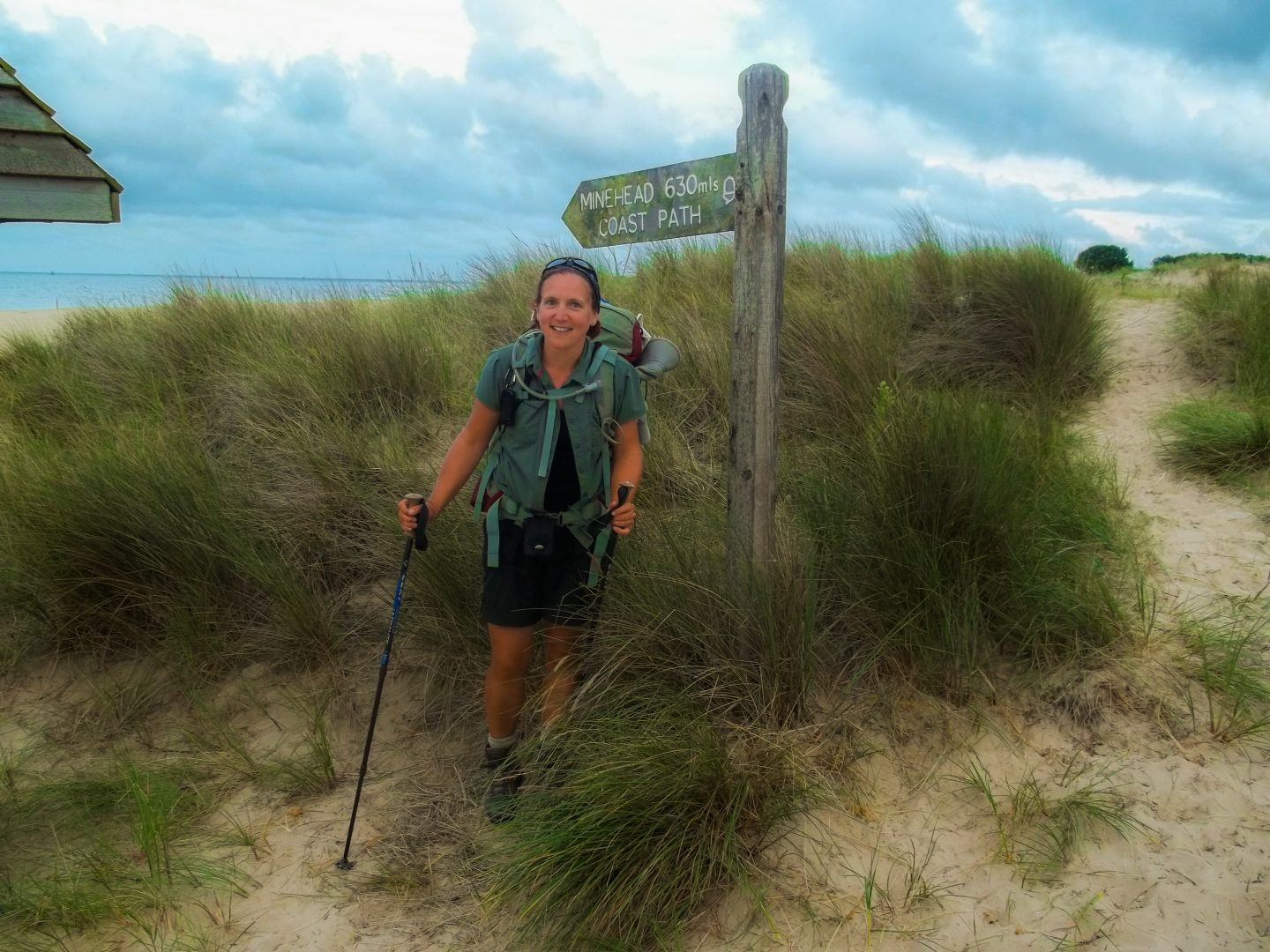 Female backpacker stands in front of a finger post smiling, having just completed a long-distance trail of 630 miles.