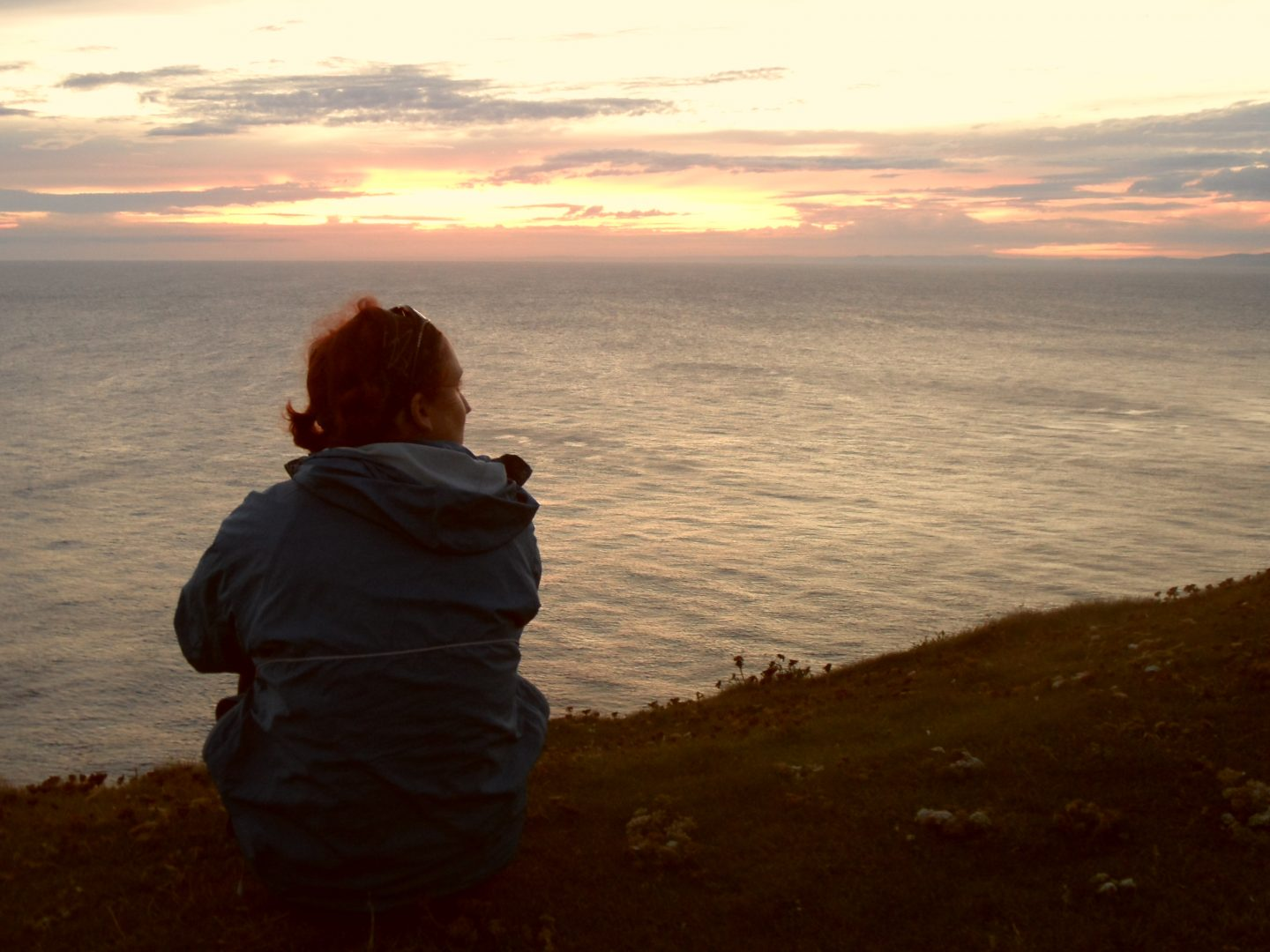 Lone female, sat on a cliff top with sea ahead and a sky beyond. Sun is setting.