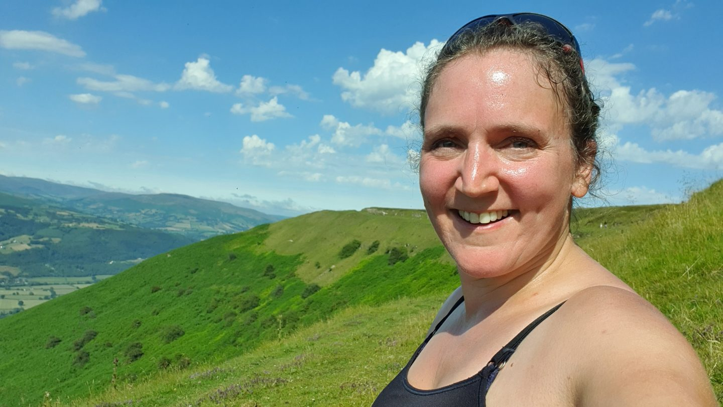 Lady sits at the top of a hill, smiling and looking hot and rosy-cheeked