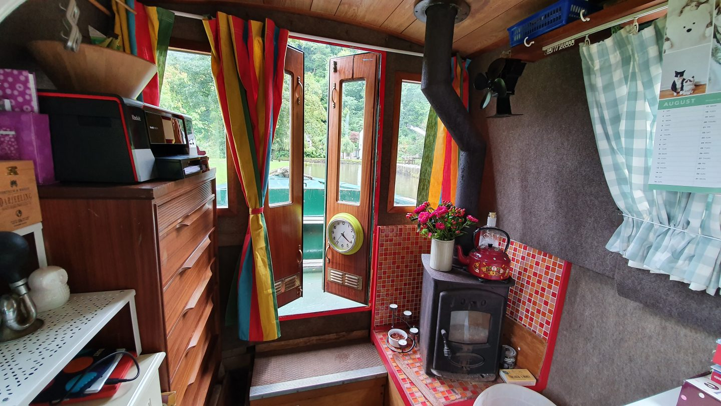 The interior of a narrowboat, looking towards the bow end (front) of the boat with a wood burner in the foreground and open doors.