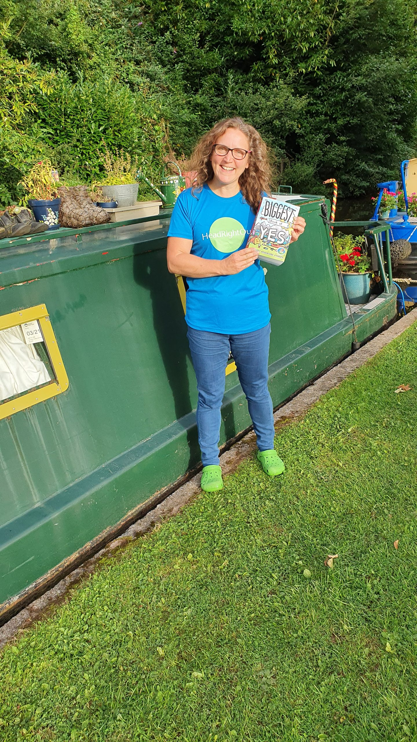 "Having said ""yes"" to boat life, a woman stands in front of a canal boat, holding up The Biggest Book of Yes"