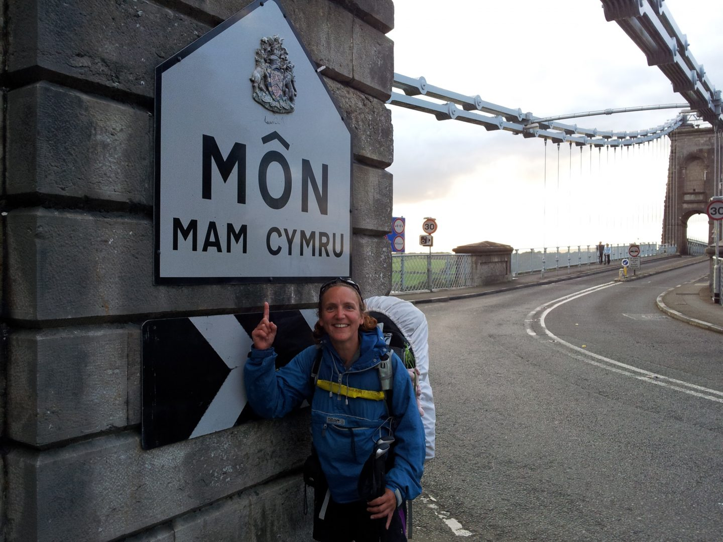 A woman standing at the start of a bridge, pointing upwards at a Mon Mam Cymru sign.