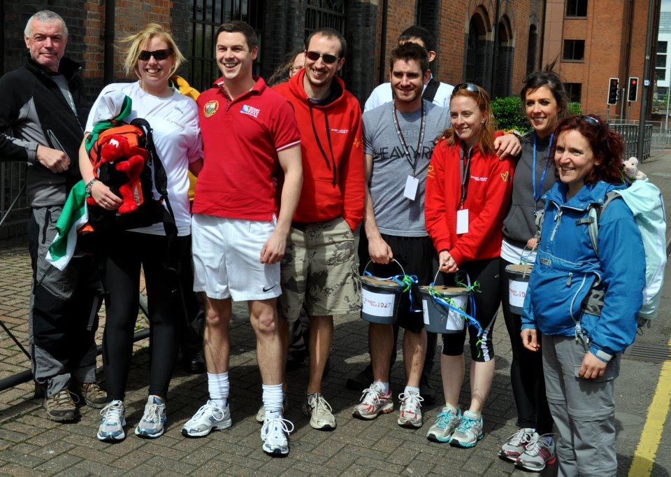 A group of people standing on a street in sports clothing and trainers