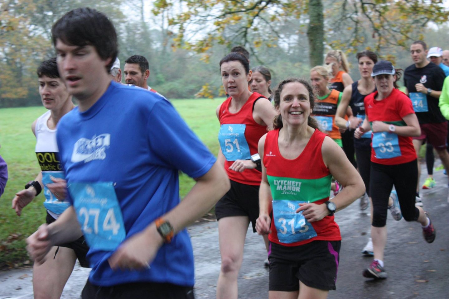 A group of runners in multicolored tee shirts and vests with Zoe in a red vest with a green band and a blue bib number (313). She smiles as she looks directly at the camera, despite this being only a few months after heartbreak and empty nest.