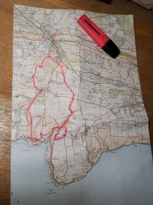 A map of the Isle of Purbeck in Dorset, UK, with a route penned out in pink highlighter pen. The pen sits in the top right-hand corner of the map. Planning using a map can help a dream become reality.