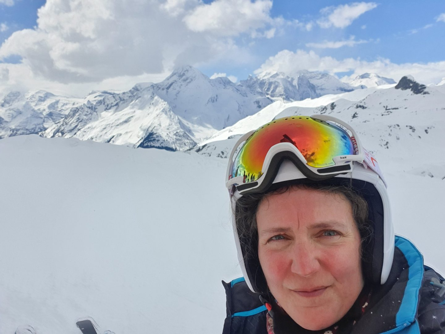Although making her dream a reality, Zoe looks at the camera with anxiety in her face. She wears a ski helmet and goggles on her head. An expanse of blue/white snow and the backdrop of the French Alps lie behind her.