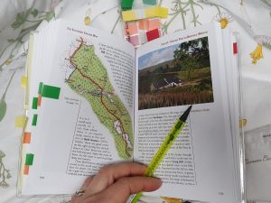 A guide book of the Southern Upland Way by Cicerone Press, with lots of page markers attached for planning. Zoe's hand sits at the bottom of the photograph, holding a pencil over the page of the book. Planning like this can help a dream to walk a national trail become a reality.