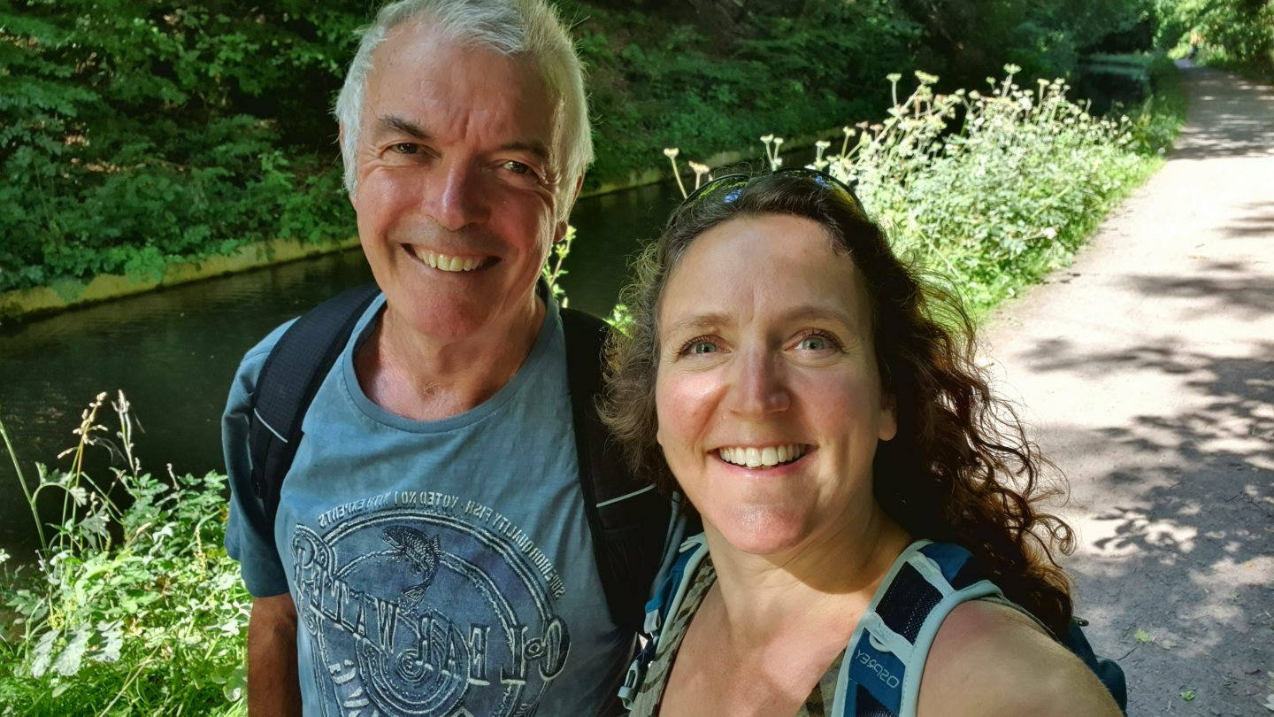 Mike and Zoe smile for a selfie while on a canal walk. The borders of the towpath behind them are filled with summer wild flowers such as cow parsley and the sun is shining brightly. Both are wearing rucksacks and Zoe's hair is curly and tumbling down her back.