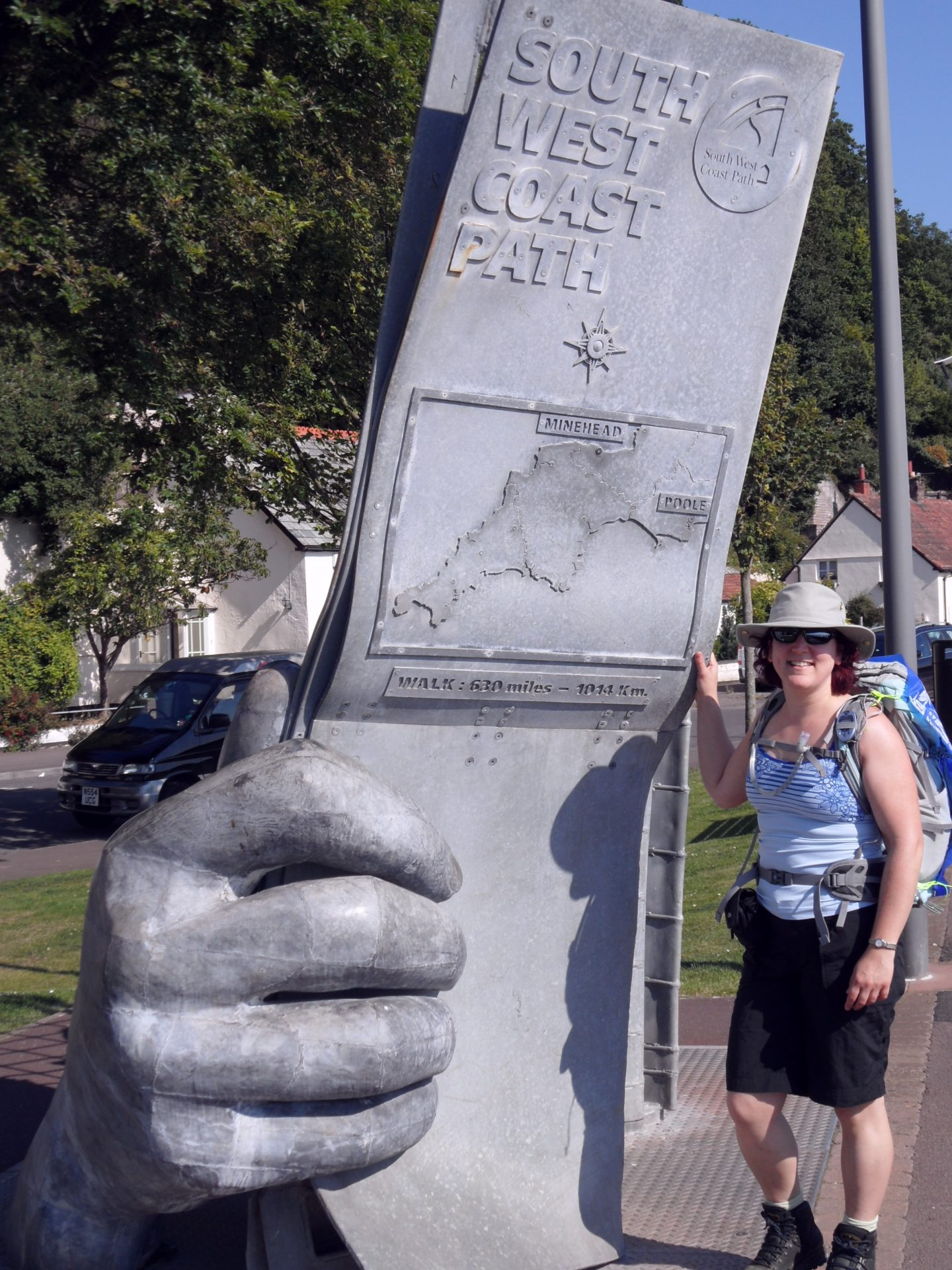 Zoe is wearing black shorts, a blue cami vest and a Tilley adventure hat and sunglasses. She stands next to a large sculpture of oversized hands, holding a partly unfolded map that is double her height. It has the words at the top, South West Coast Path.