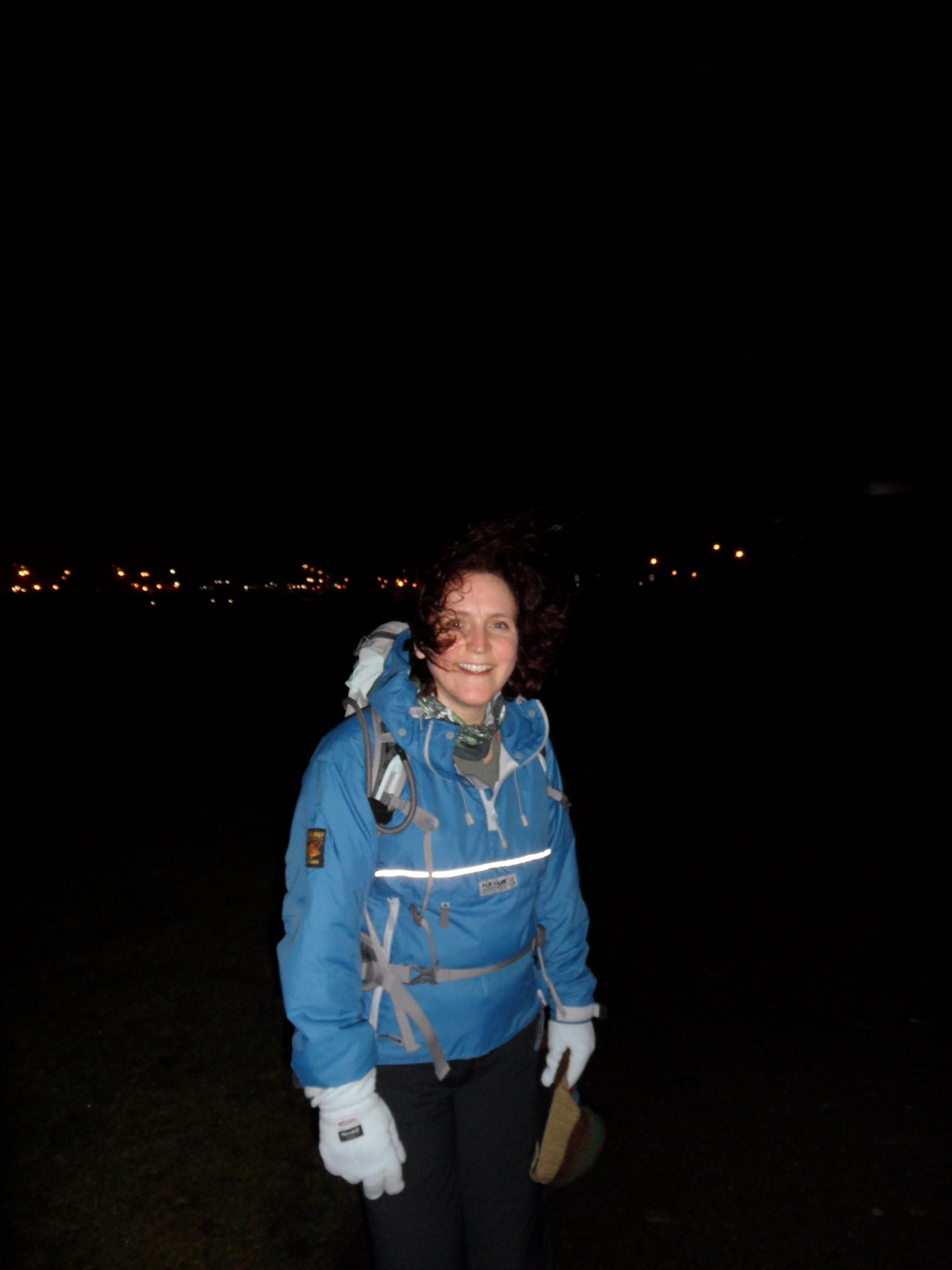 Zoe is standing outside, at night with her hair windswept but wearing a broad smile. Her blue, waterproof smock, gloves and woolly hat in her hand suggests it's a cold night but she's happy, training for her dream and unbeknown to her, also training for how to cope with heartbreak and her empty nest.