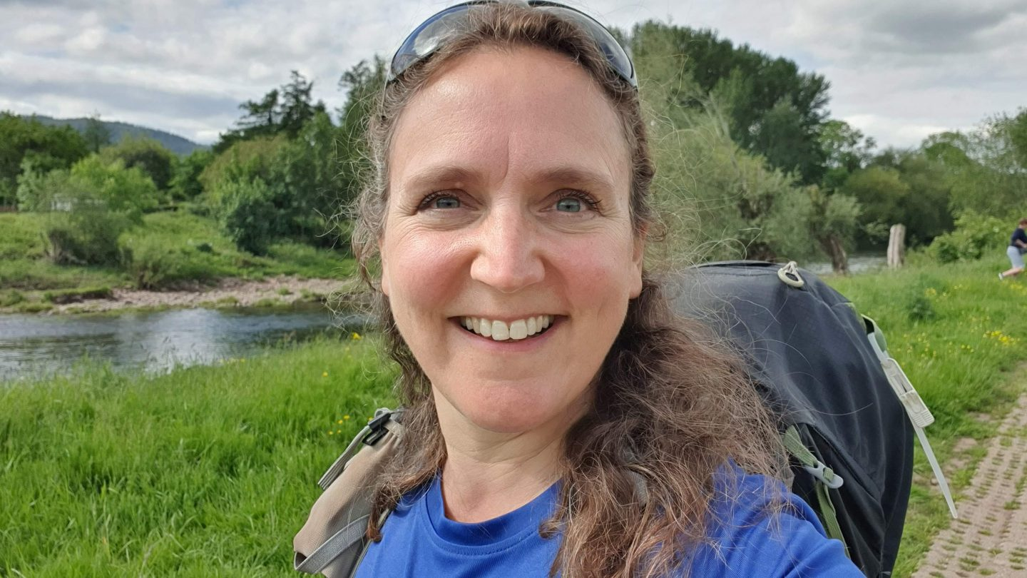 A woman, Zoe, smiling at the camera, with sunglasses on her head, curly hair tumbling over her shoulder and wearing a rucksack and blue t-shirt. There is a river, grass, trees and a hill in the background.